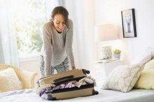 Une femme prépare sa valise pour un voyage.