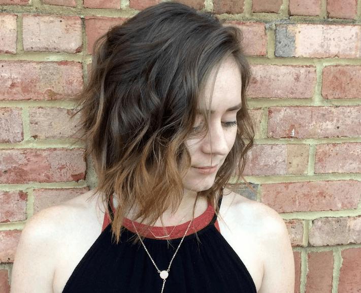 Femme aux cheveux ébouriffés coupés au carré avec un collier noir à dos nu Instagram.