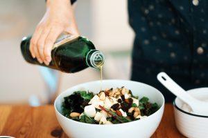 Femme versant de l'huile d'olive sur une salade