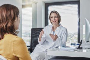 Femme parlant au médecin généraliste après s'être demandée pourquoi je n'arrive pas à tomber enceinte.