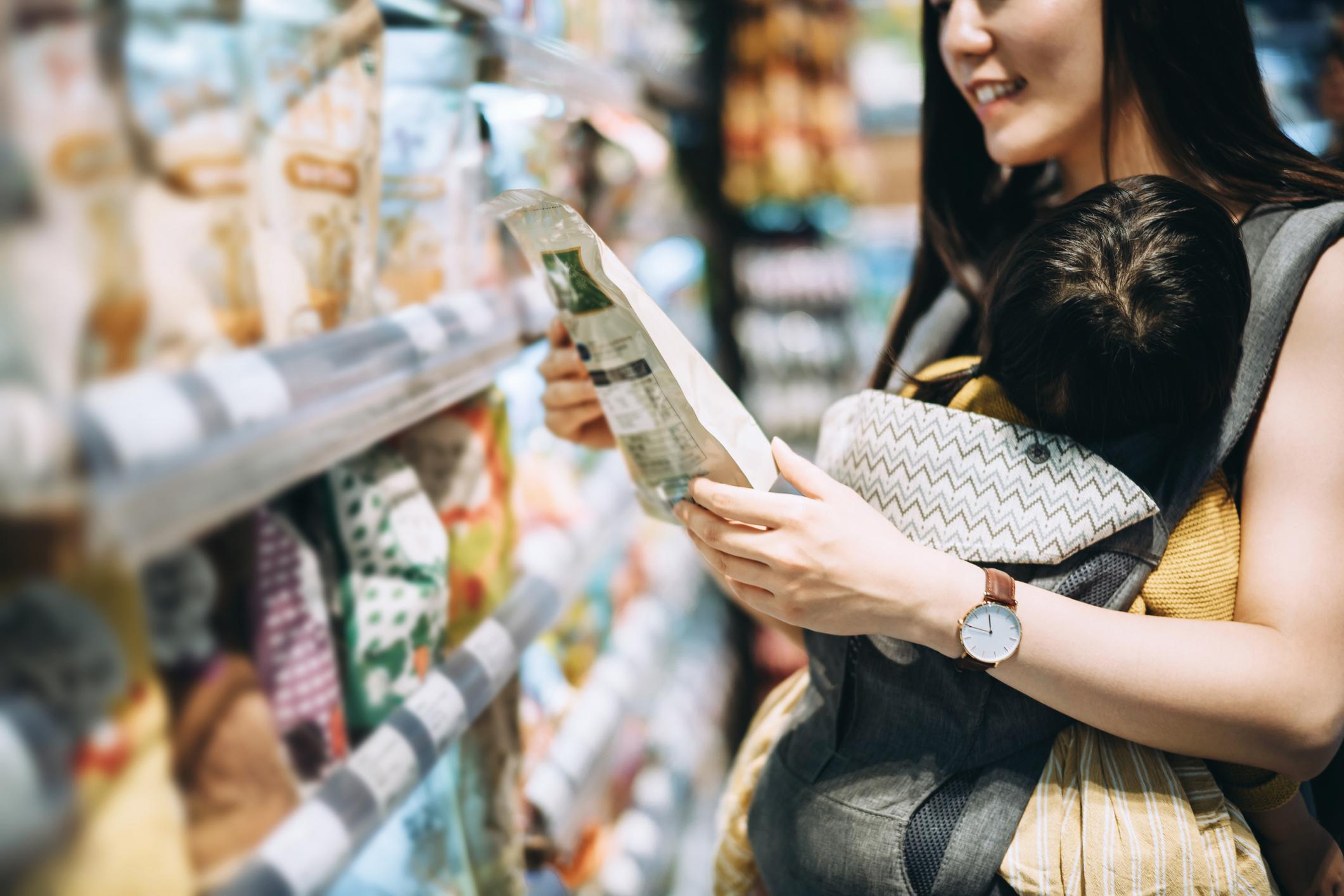 Une femme vérifie l'emballage des céréales pour voir si le granola est sain.
