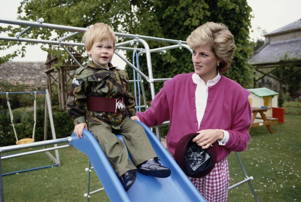 Le prince Harry portant l'uniforme du régiment de parachutistes de l'armée britannique dans le jardin de Highgrove House dans le Gloucestershire, le 18 juillet 1986. Il est accompagné de sa mère, Diana, princesse de Galles.