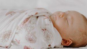 bébé dans un berceau aden et anais