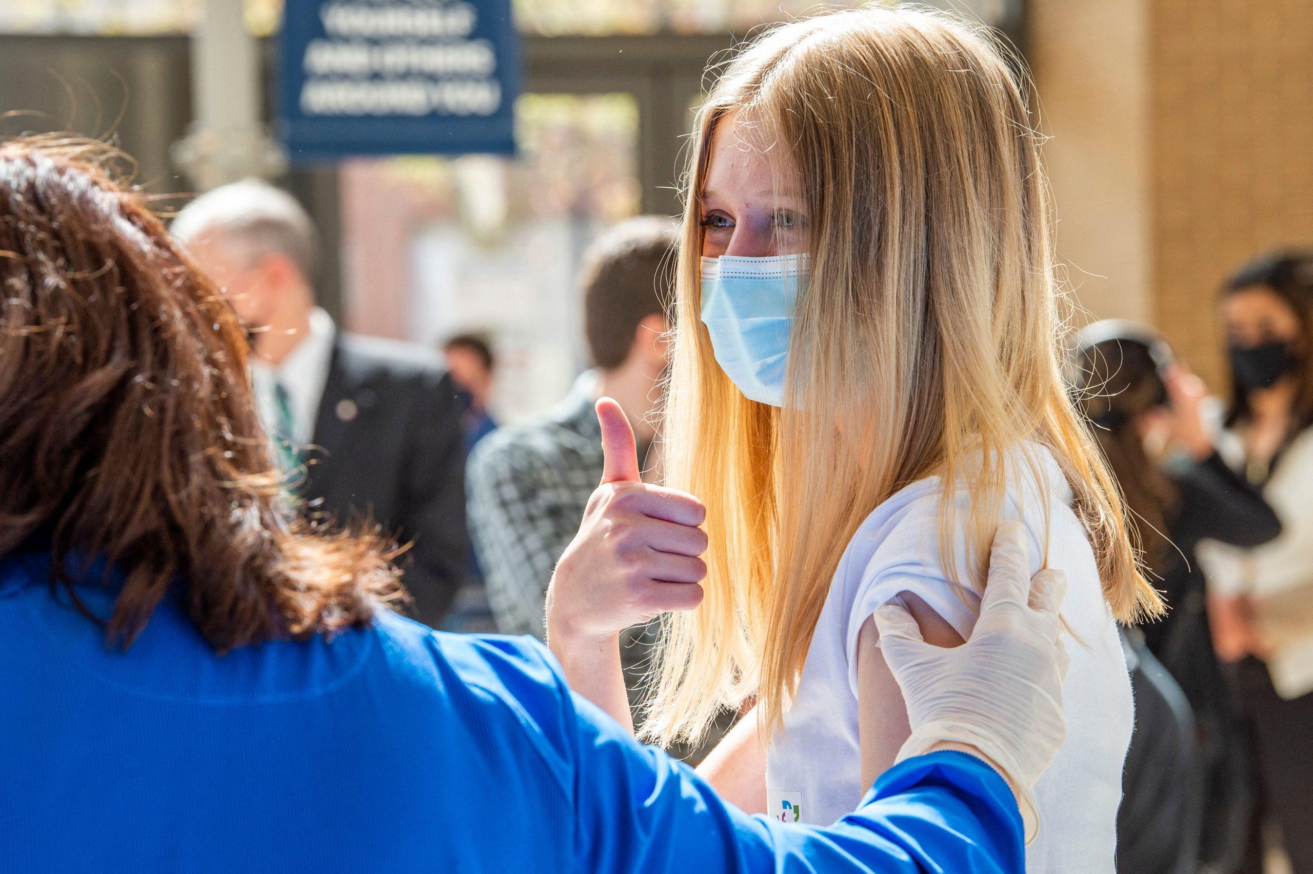 Une jeune fille blonde lève le pouce aux États-Unis alors qu'on répond aux questions concernant la date à laquelle les enfants recevront le vaccin contre le coronavirus au Royaume-Uni.