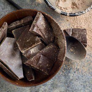 Plaques de chocolat dans un bol avec une cuillère et de la poudre sur le côté.