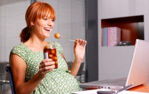 Femme enceinte mangeant des oignons marinés sur un bâton.