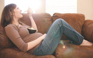 Femme enceinte mangeant une glace en raison d'une envie de grossesse.