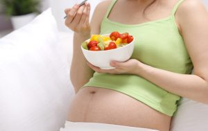 Femme enceinte mangeant un fruit