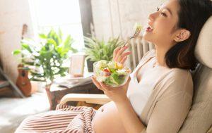 Femme enceinte au ventre découvert mangeant de la salade