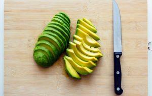 Avocat coupé en tranches sur une planche avec un couteau.