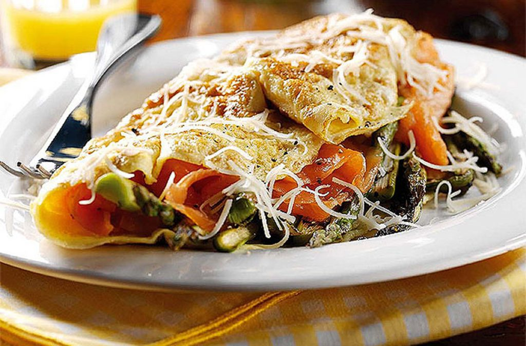 Omelette au saumon fumé et aux asperges sur une assiette blanche
