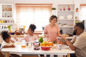 Famille à la table du petit-déjeuner mangeant des Weetabix, des fruits et du jus de fruits.