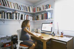 Femme regardant son ordinateur portable et téléphonant dans un bureau à domicile, faisant des recherches sur les effets du vaccin contre le covid et la grossesse.
