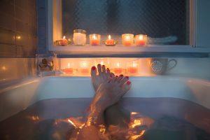 Gros plan sur les pieds d'une femme dans un bain avec des bougies.