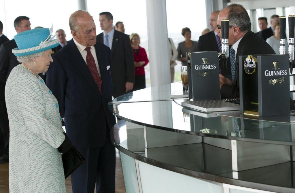 La reine Elizabeth II et le prince Philip, duc d'Édimbourg, regardent une pinte de Guinness en train d'être versée lors de leur visite de la Guinness Storehouse, le 18 mai 2011 à Dublin, en Irlande.