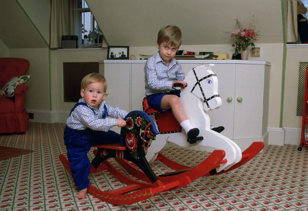 Le Prince William et le Prince Harry jouent sur un cheval à bascule dans leur salle de jeux au Palais de Kensington.