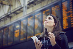 Femme à l'aéroport regardant son téléphone et portant des écouteurs.