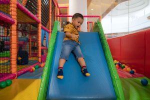 Un petit garçon descend le toboggan d'une aire de jeux à la réouverture.
