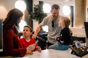 Des parents et des enfants souriants se présentent à l'hôtel après la réouverture de l'établissement.