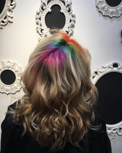 femme aux cheveux bruns ondulés et aux racines arc-en-ciel