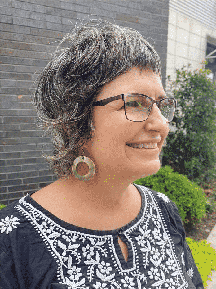 Femme de plus de 50 ans avec des cheveux fins et une coupe au rasoir avec des lunettes.