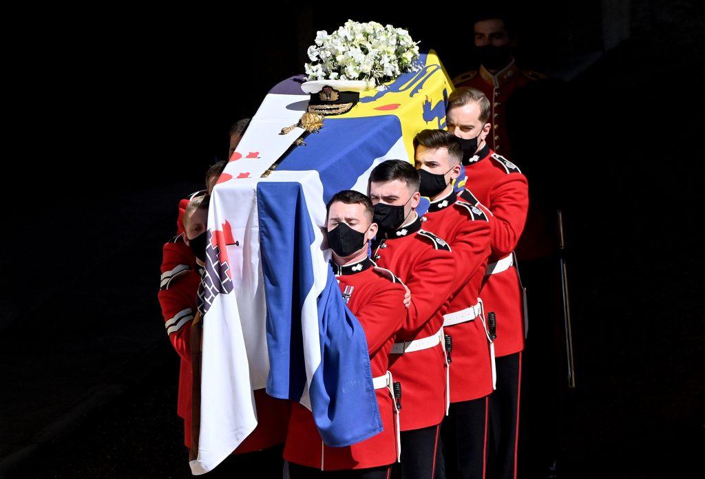 Un groupe de Grenadier Guards porte le cercueil du Prince Philip, Duc d'Édimbourg (drapé de son drapeau royal et portant sa casquette de la Royal Navy, son épée et un bouquet de lys, de roses blanches, de freesia et de pois de senteur) hors de l'entrée d'État du château de Windsor avant la procession funéraire vers la chapelle Saint-Georges du château de Windsor le 17 avril 2021 à Windsor.