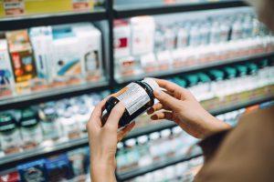 Une femme regarde des analgésiques au supermarché.