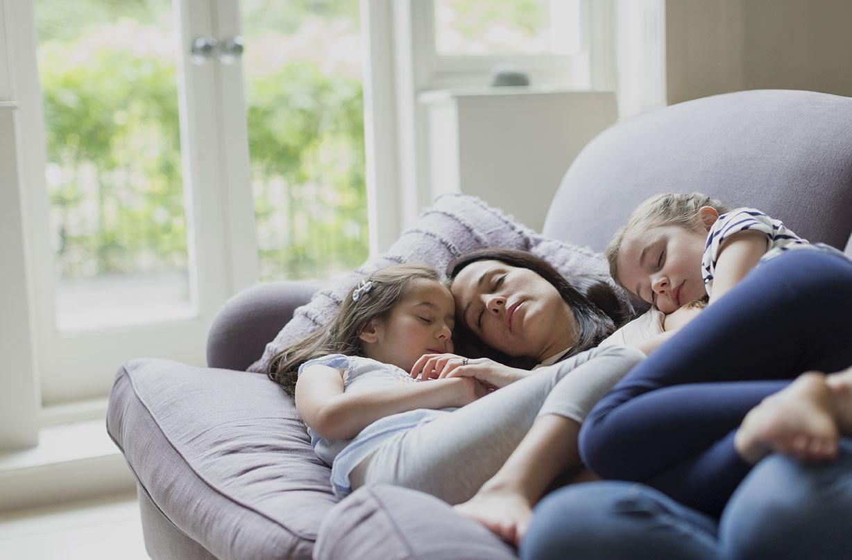 Parent et enfants endormis sur le canapé