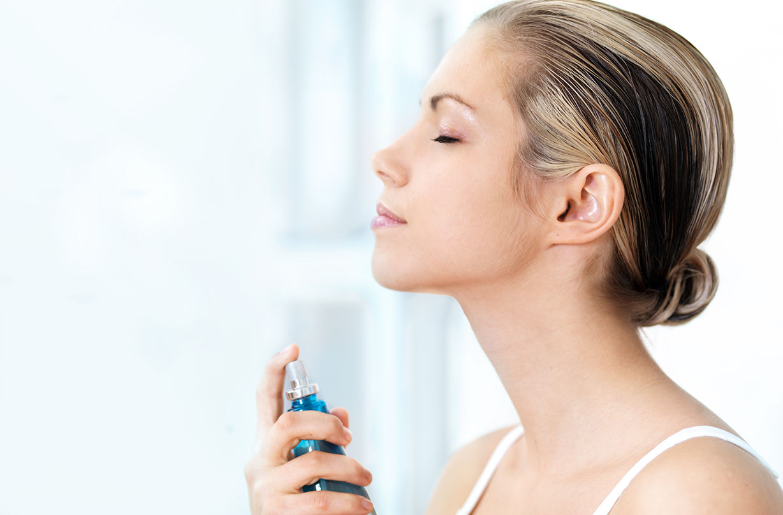 Une femme vaporisant un spray rafraîchissant sous la chaleur.