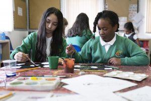 Deux enfants s'adonnant à l'art à l'école alors que des projets d'allongement de la journée scolaire sont dévoilés au Royaume-Uni.