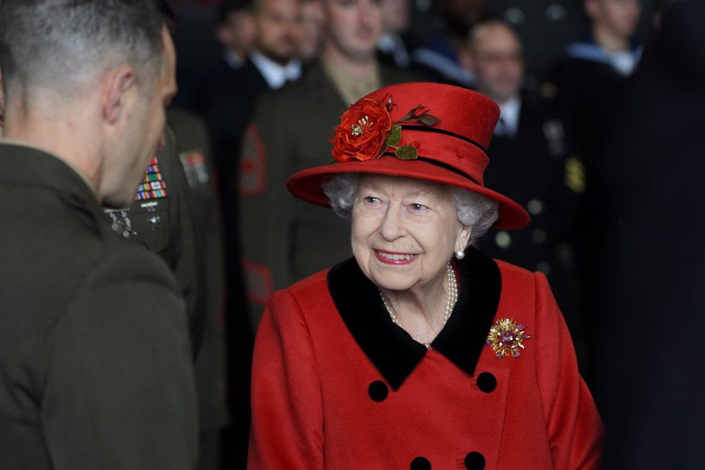 La reine Elizabeth II s'entretient avec du personnel militaire lors d'une visite du HMS Queen Elizabeth à la base navale de HM avant le déploiement inaugural du navire, le 22 mai 2021 à Portsmouth, en Angleterre.