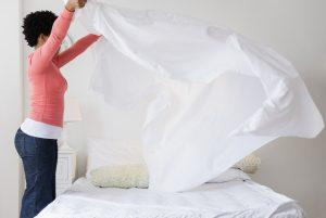 Femme faisant son lit