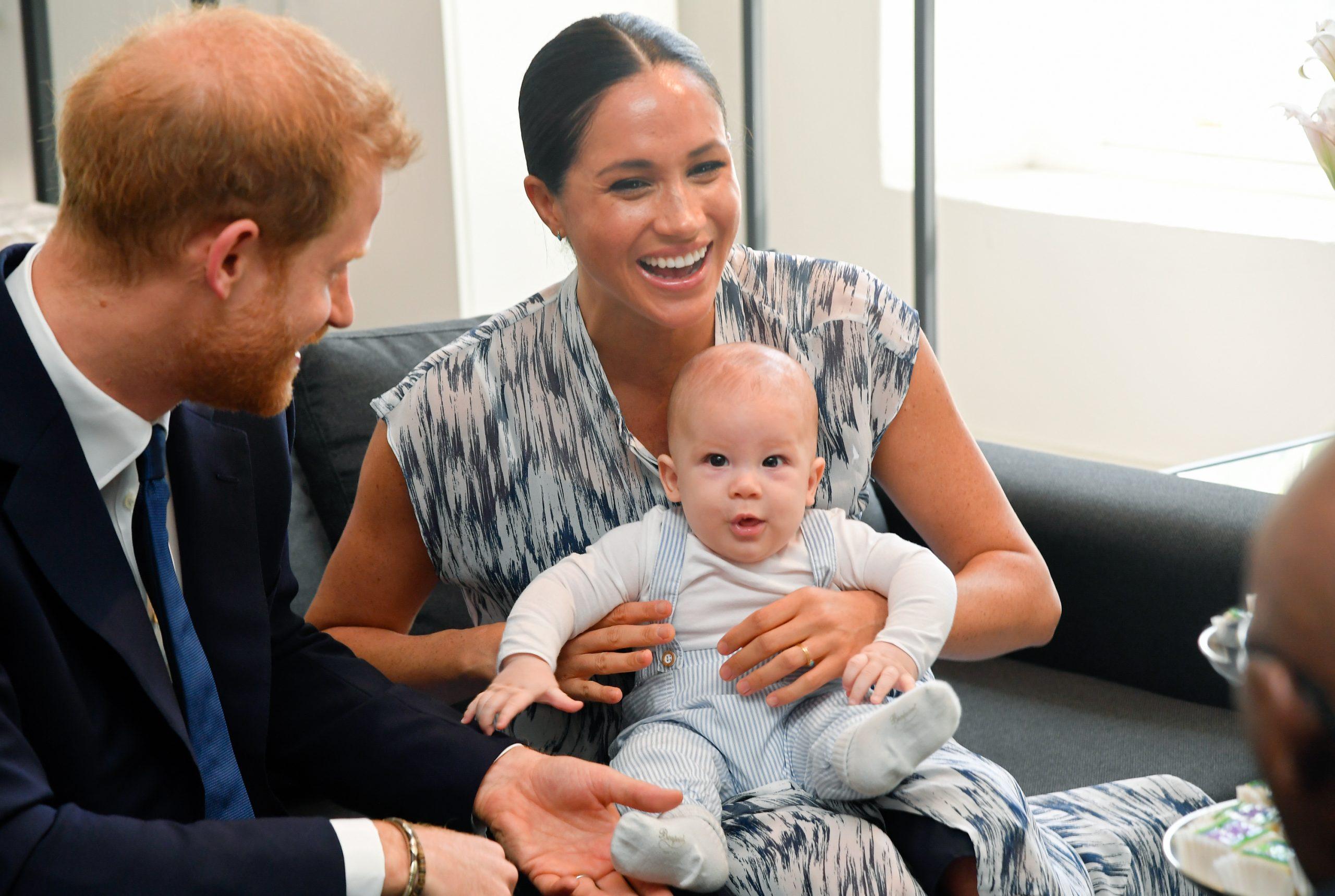Meghan tient son fils Archie dans ses bras sous le regard du Prince Harry.