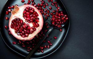 Une demi-grenade avec des graines éparpillées sur une assiette - des fruits à faible teneur en calories.