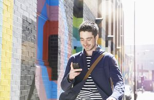 Homme marchant dans la rue, souriant, avec un texte sur fond de mur coloré.