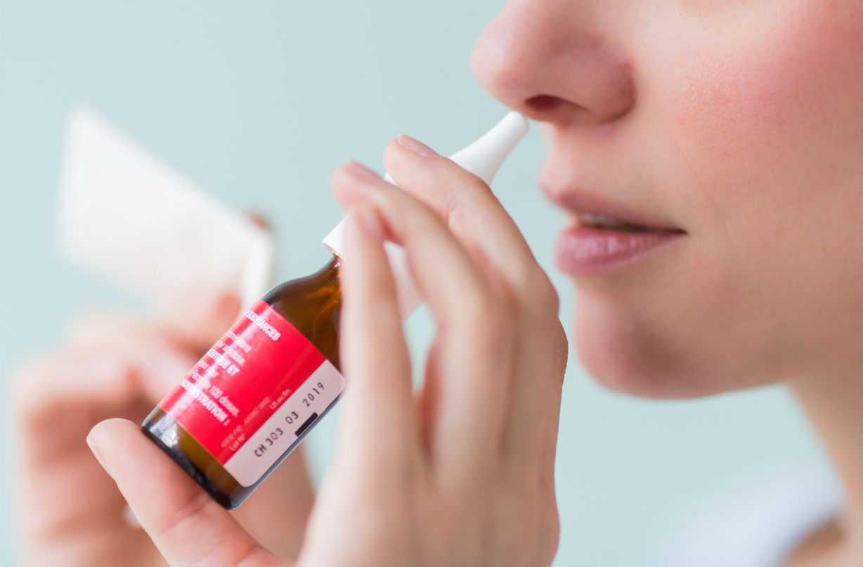 Gros plan d'une femme utilisant un spray nasal.