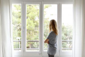 Femme en t-shirt gris regardant par la fenêtre, dos à la caméra.