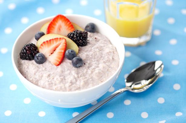 Bol de petit-déjeuner bircher museli noircur avec fraises, myrtilles et mûres à côté d'un verre de jus d'orange sur une nappe à pois noirs.