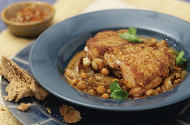 poulet et pois chiches dans un bol gris avec du pain