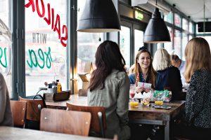 Des amis souriants dans un restaurant après la fin du confinement selon le dernier plan du gouvernement.