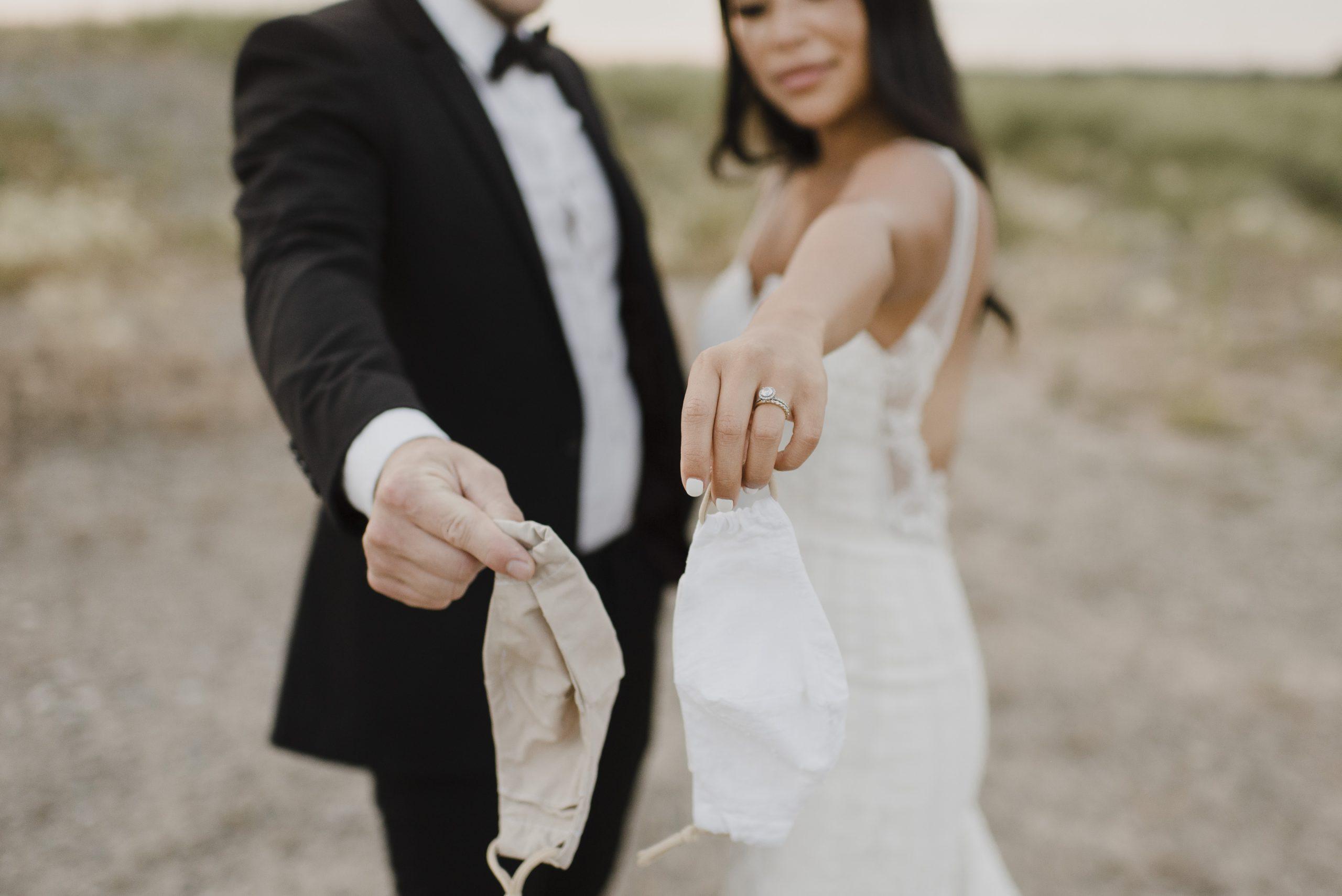 Un couple de mariés brandissant des masques faciaux faisant partie des nouvelles règles de verrouillage des mariages.