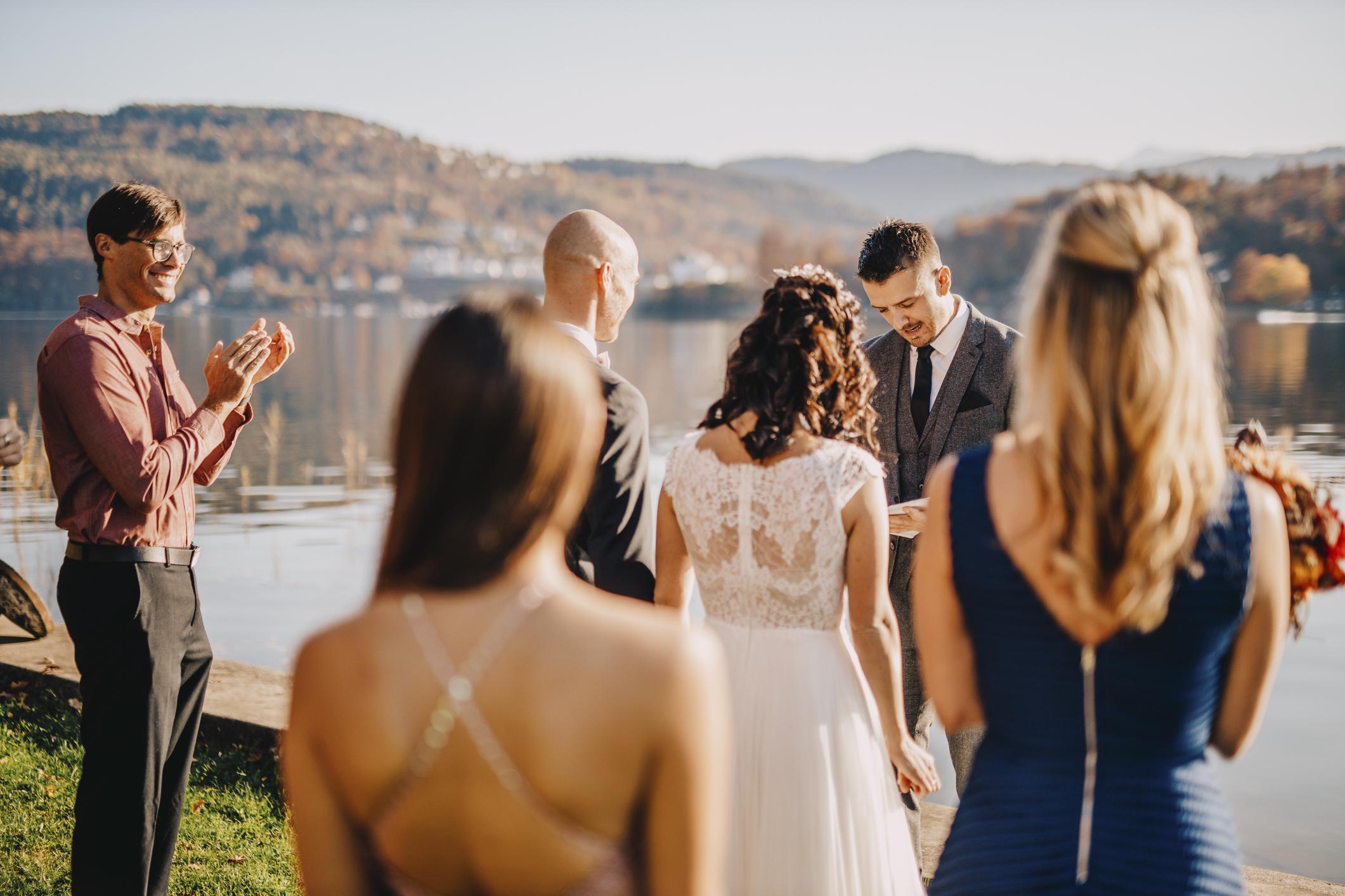 Un groupe d'invités à un mariage regardant une mariée et un marié se marier.