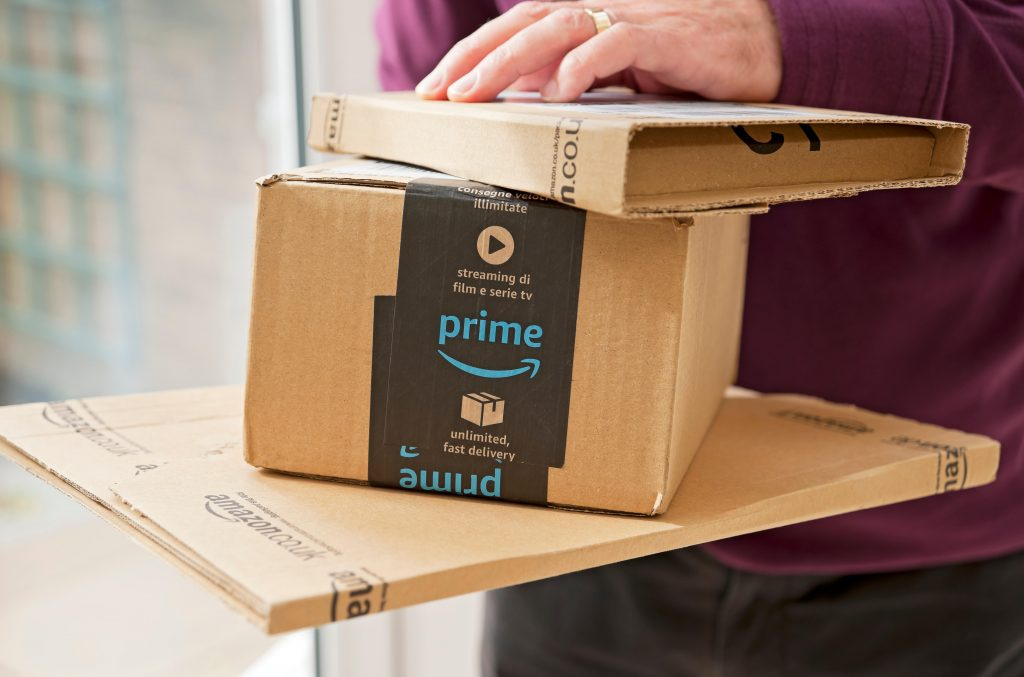 Close up of man holding Amazon prime packages package box home internet shopping delivery