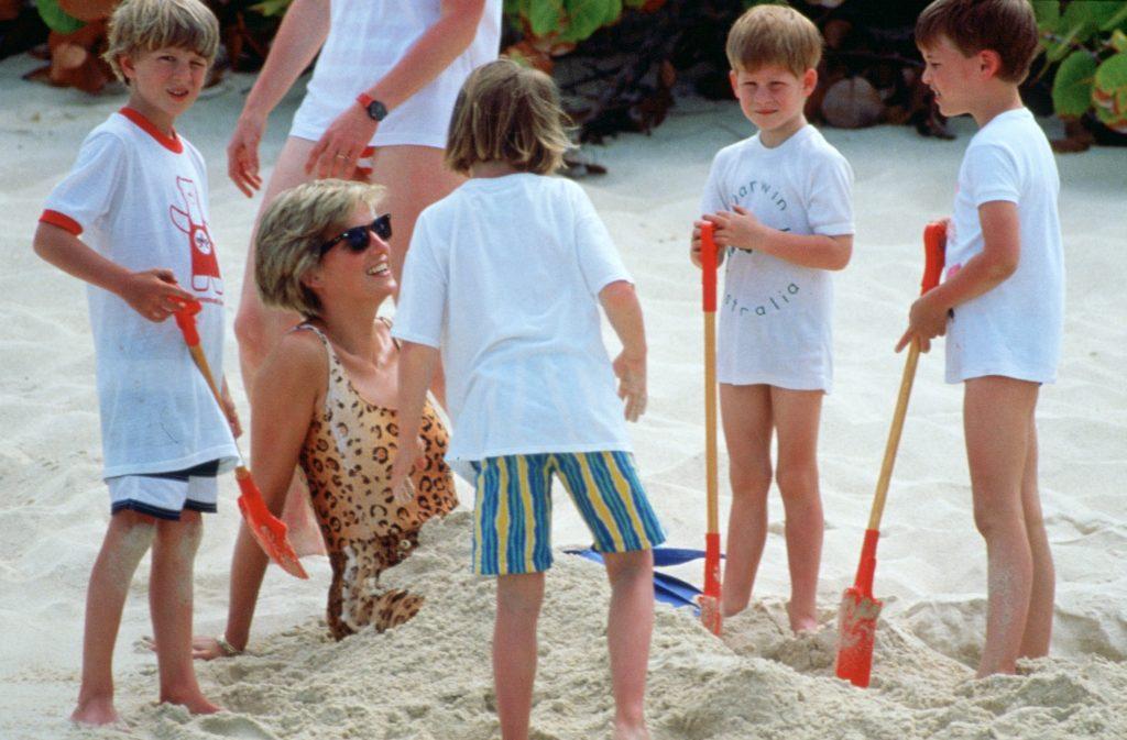Diana, princesse de Galles, est enterrée dans le sable par ses fils, le Prince William et le Prince Harry, lors de vacances sur l'île Necker. La Princesse Diana porte un maillot de bain léopard.