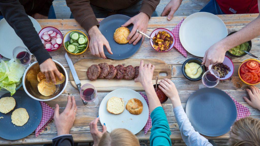 Famille mangeant des hamburgers à une table de bière - photo d'archive