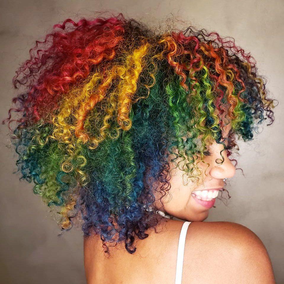 Femme aux cheveux naturels bouclés teints en couleurs arc-en-ciel.