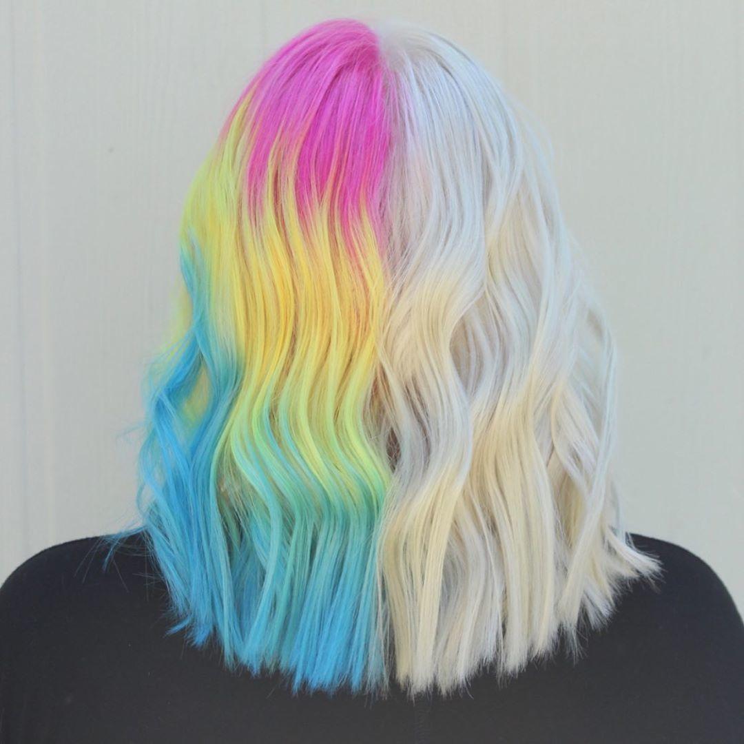 Femme avec des cheveux moitié blond glacé et moitié arc-en-ciel.