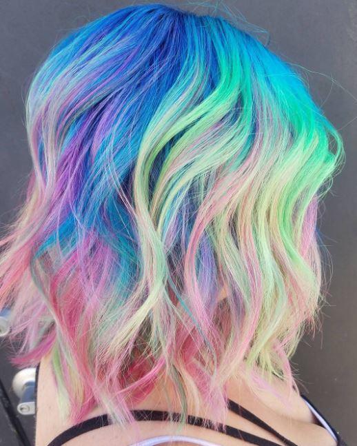 Cheveux arc-en-ciel fluo - cheveux longs ondulés de couleur arc-en-ciel vus de côté.