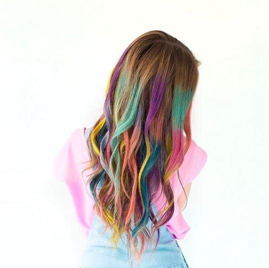 femme avec des cheveux châtain clair et des couleurs arc-en-ciel ajoutées sur ses longueurs
