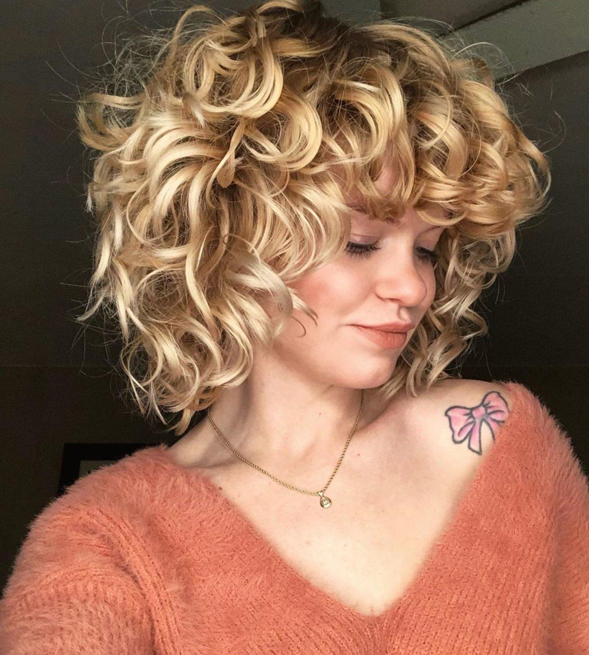 La coupe blonde bouclée avec frange